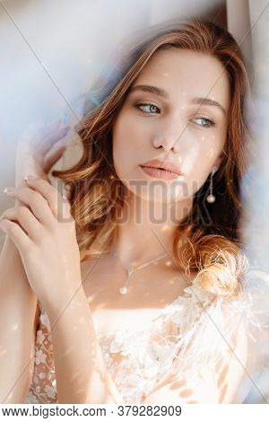 Close-up. The Sun Glare. Portrait Of A Beautiful Young Woman With Long Hair In White Dress.