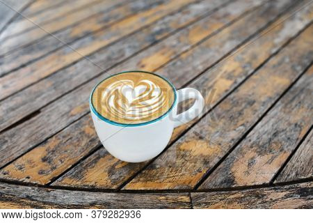 Cup Of Fresh Creamy Cappuccino With Latte Art On Foam. Background Of Brown Wooden Table With Shabby