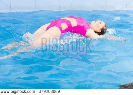 Beautiful Young Woman In Pink Swimsuit Swimming In Blue Pool On Her Back. Young Female Swimmer At Ho