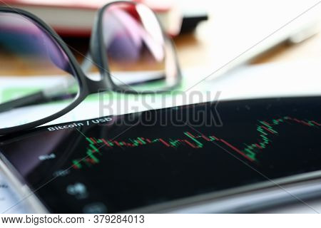 Close-up Of Stock Market Bar Chart. Bitcoin Rate. Glasses And Smartphone Lying On Desk. Analysing Pr