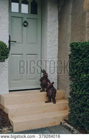 Broadway, Uk - July 07, 2020: Metal Statues By Front Door Of A Traditional English House In Broadway