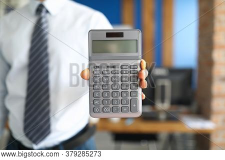 Closeup Of Businessman Holding Grey Calculator In Camera. Person Wearing Suit Posing Indoors. Profes