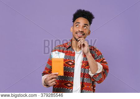 Pensive Young African American Guy In Colorful Shirt Traveling Abroad Isolated On Violet Background.