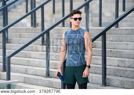 Sportsman Wearing Sunglasses And Wearable Device Technology Watch While Exercising. Muscular Athlete