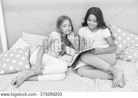 Book About Love. Girls Children Lay Bed Read Book. Pleasant Time In Cozy Bedroom. Girls Sisters Cute