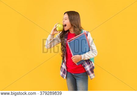 Feed Your Imagination. Little Girl Bite Apple Yellow Background. School Snack. Healthy Eating Habits