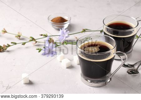 Chicory Beverage In Two Glass Cups, With Concentrate And Flowers On Grey Background. Healthy Herbal
