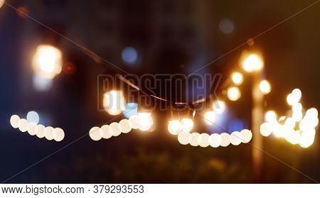 Photo Of String Lights Hanging On Tree In The Garden At Evening Time. Fashion Decoration With Bulbs