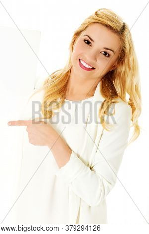 Suprised woman showing something, for exaple product with her finger.