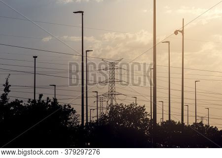 Silhouette High Voltage Tower And Lampposts, At Sunset