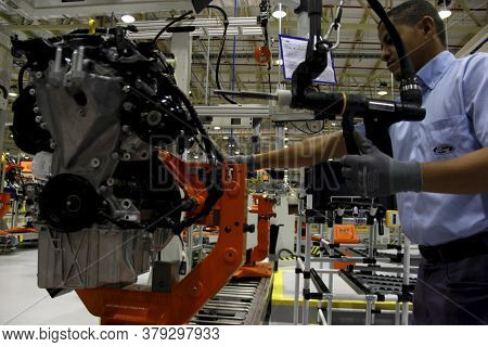 Camacari, Bahia / Brazil - April 9, 2014: Worker Working On The Engine Assembly Line Of The Ford Fac