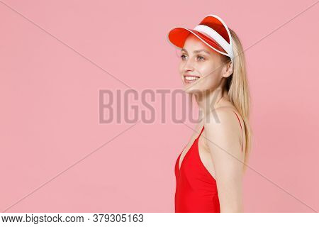 Side View Of Smiling Young Blonde Woman Girl In Red One-piece Swimsuit Cap Posing Isolated On Pink B