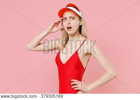Shocked Perplexed Young Blonde Woman Girl In Red One-piece Swimsuit Cap Posing Isolated On Pink Back