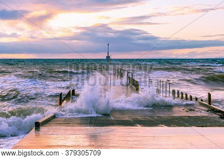 Large Wave Splashes Protruding Through Boat Jetty On Ocean Coastline At Sunset