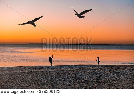Silhouettes Of Children Playing On Ocean Beach At Sunset With Birds Flying And City Skyscrapers In T