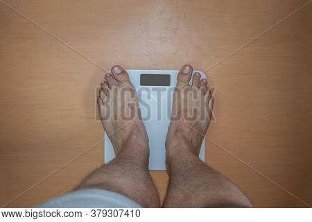 Fat Man Weighing Himself On Digital Scale