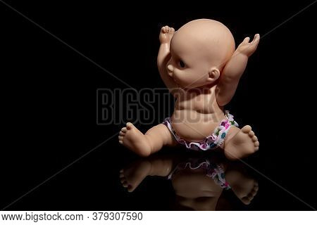 Little Plastic Doll Baby On Black Background