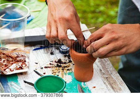 A Man Prepares A Hookah In The Open Air In Summer On The Background Of A Light Table. Preparation Of