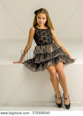 A Beautiful Little Girl In A Stylish Dress Sits On A White Parapet. Studio Photography.
