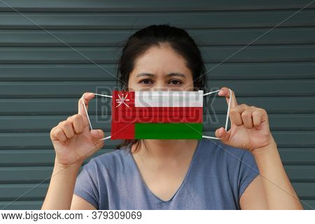 A Woman With Oman Flag On Hygienic Mask In Her Hand And Lifted Up The Front Face On Dark Green Backg