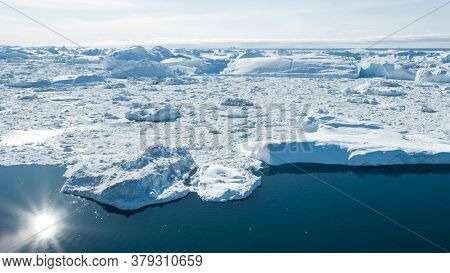 Iceberg aerial drone image - Global warming and climate change concept. Giant icebergs in Disko Bay on greenland in Ilulissat icefjord from melting glacier Sermeq Kujalleq Glacier, Jakobhavns Glacier.