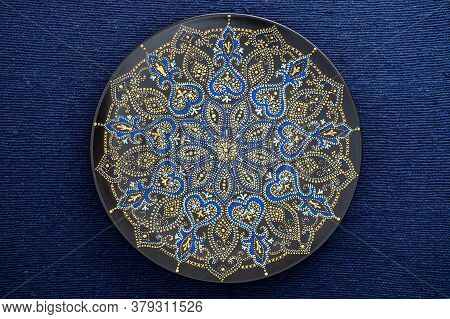 Decorative Ceramic Plate With Black, Blue And Golden Colors, Painted Plate On Background Of Fabric,