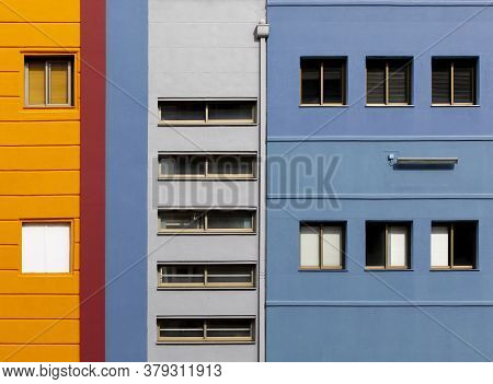 Multi-colored Facades Of The School With Black Window Frames. Look Up From The Blue Sky, Colored Bui