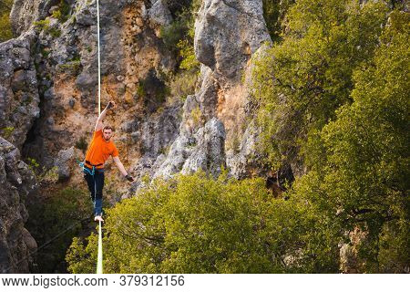 A Man Is Walking Along A Stretched Sling. Highline In The Mountains. Man Catches Balance. Performanc