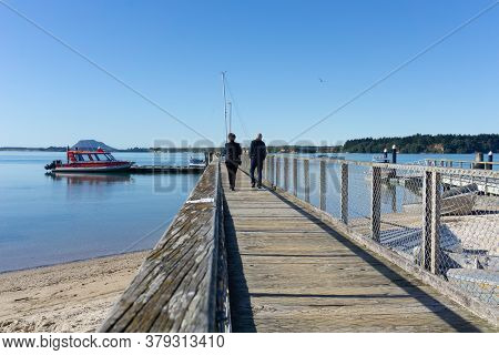 Tauranga New Zealand - July 27 2020; Omokoroa Waterfront With Two People Walking Away On The Pier.