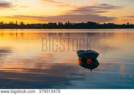 Clinker Dingy Moored To Bright Orange Buoy On Calm Water In Bay With Golden Sunrise.