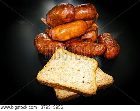 Smoked Meat Sausages With Bread On A Black Background. Food Photo. Recipe. Smoked Meat. Fatty Food.