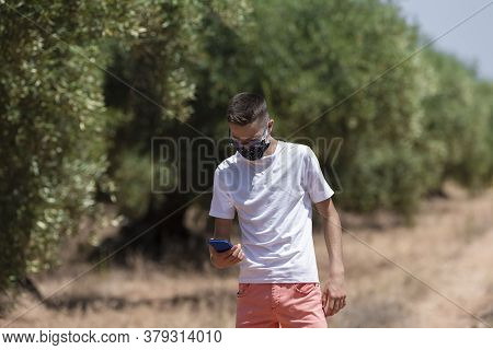 A Young Man Using A Face Mask Looking Down At His Phone On An Out Of Focus Nature Background