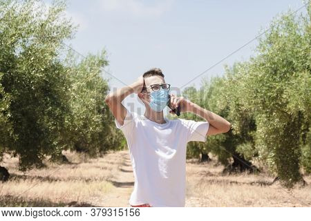 Young Man Wearing A Surgical Mask Holding His Head While Talking On His Phone