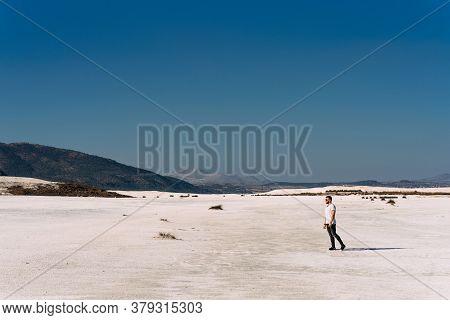 A Man Walks Along The Shore Of Lake Salda In Turkey. Single Man Walking Alone Into The Desert. A Man