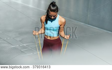 Healthy Fit Woman Exercising With Resistance Band On A Sunny Day Outdoor. Athelte Female Working Wit