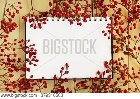 Autumn Mock Up.autumn Flat Lay. Blank Notebook And Branches With Red Berries On A Yellow Wooden Back