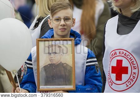 Belarus, The City Of Gomil, May 9, 2019. Victory Day. Immortal Regiment. A Boy With Portraits Of Rel