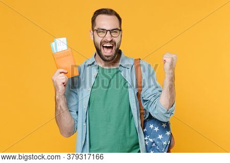 Happy Young Man Student In Glasses Backpack Hold Books Isolated On Yellow Background. Education In U