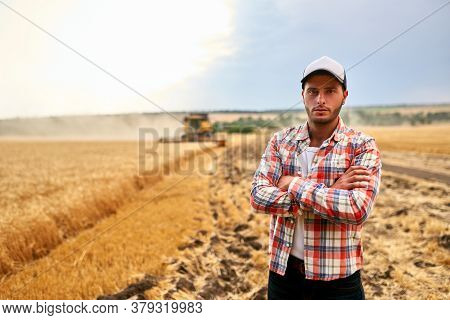 Happy Farmer Proudly Standing In A Field With Arms Crossed On Chest. Combine Harvester Crop Rich Whe