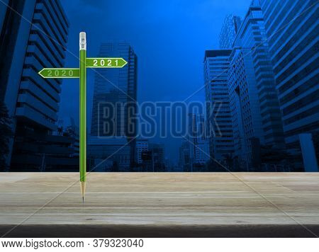 2021 And 2020 Direction Sign Plate With Green Pencil On Wooden Table Over Modern Office City Tower A