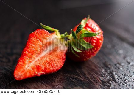Strawberry Close-up On A Black Background. Macrophotography Of Cut Strawberries. Ripe, Fragrant Stra