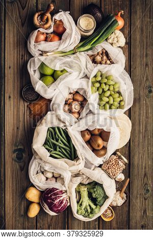 Zero waste concept. Eco bags with fruits and vegetables, glass jars with beans, lentils, pasta. Eco-friendly shopping and cooking concept, flat lay