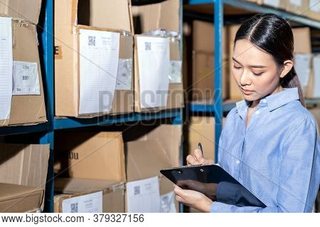 Close up of Asian smart businesswoman working with product inventory in distribution warehouse. For business warehouse inventory and logistic concept.