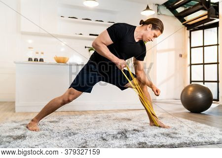 White caucasian fit sporty muscular man doing exercise with stretching band in living room at home for mental health and meditation. Working out fitness sport and healthy lifestyle concept.