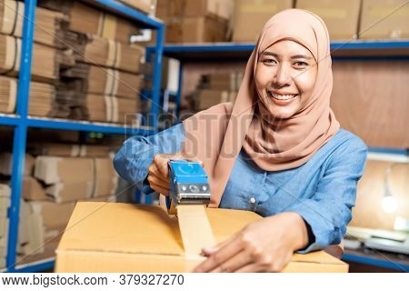 Portrait of Islam Muslim female asian warehouse worker packing and labelling on cardboard box in warehouse environment. Using in business warehouse logistic concept.