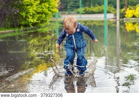 Little Cute Playful Caucasian Blond Toddler Boy Enjoy Have Fun Playing Jumping In Dirty Puddle Weari