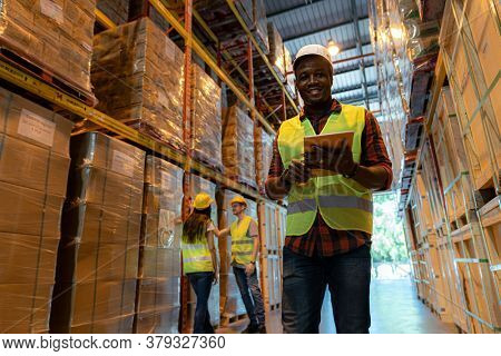 Portrait african black warehouse supervisor stand with digital tablet in large warehouse distribution center with worker work on inventory in background. Business warehouse and logistic concept