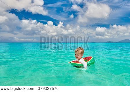 Three year old toddler boy on beach at Seychelles swimming with inflatable ring