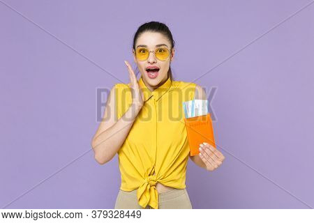Shocked Young Woman Girl In Yellow Shirt Isolated On Violet Background. Passenger Traveling Abroad T