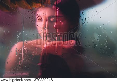 Art Portrait. Rain Beauty. Sensual Woman Face Blur Silhouette In Neon Red Bokeh Light Behind Steamed